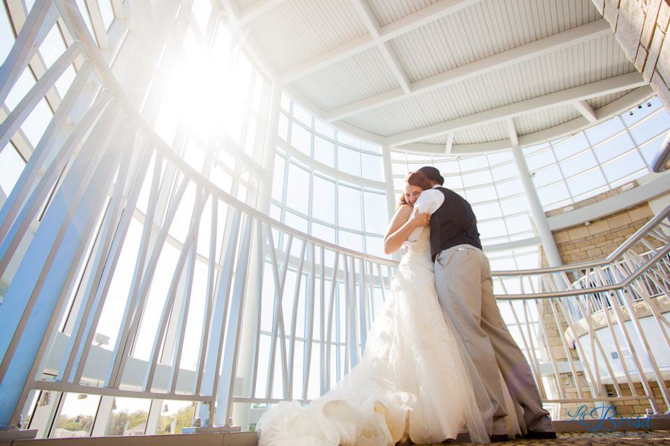 A bride and groom embracing in a room full of windows with the sun shining through
