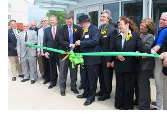 A group of men and women performing a ribbon cutting ceremony