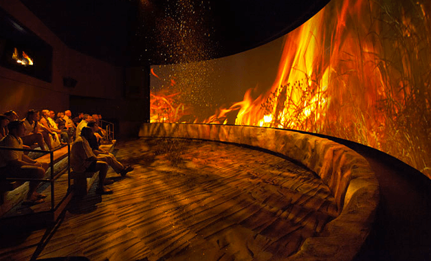 A wide movie screen showing a prairie fire while ashes fall from the ceiling