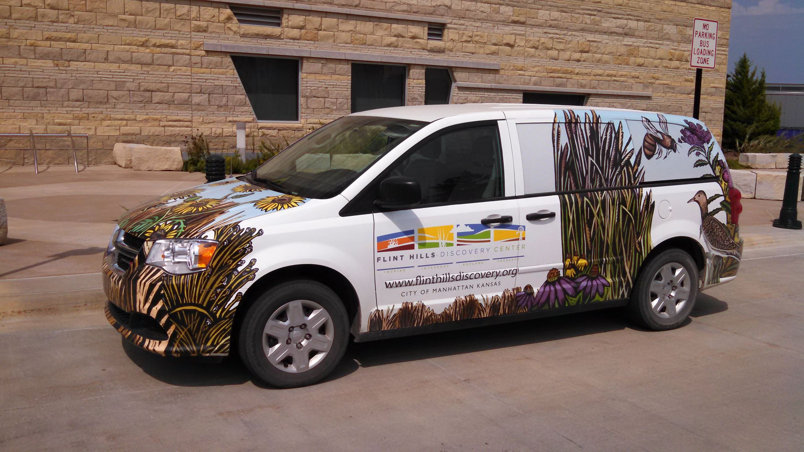 A van decorated with images of Flint Hills native grass